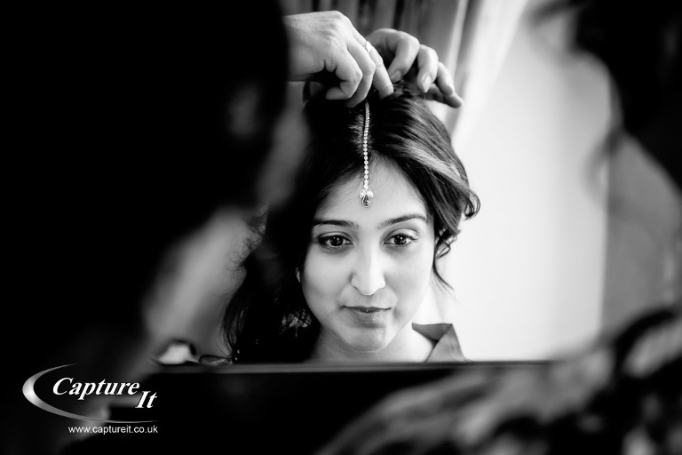 asian bride looking in a mirror as her jewellery is put on