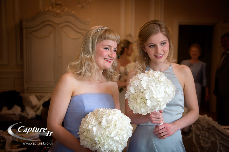 Bridesmaids hold bouquets of pure white flowers