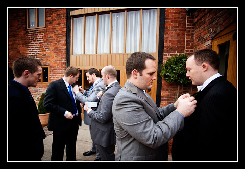 Groom and ushers putting on buttonholes