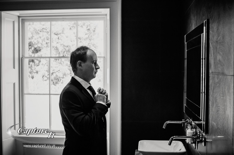 atmospheric black and white photo of groom adjusting his tie