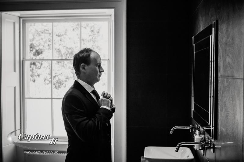 atmospheric black and white photo of groom adjusting his tie