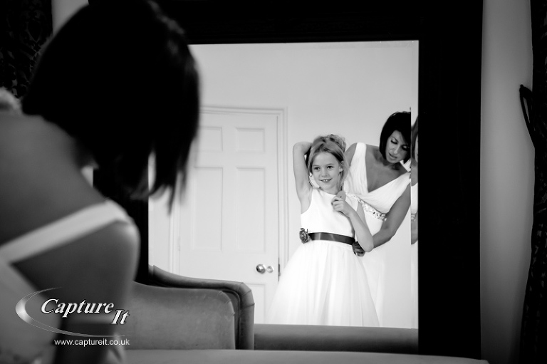 bride helps flower girl get ready