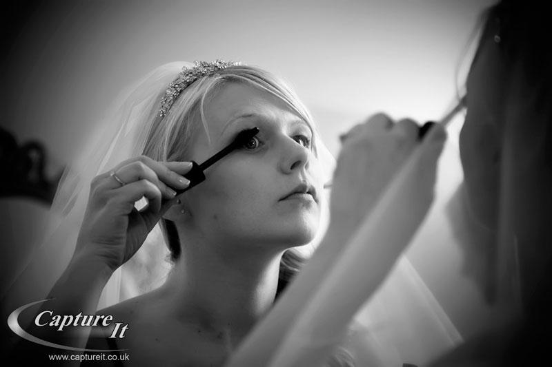wedding photo of bride putting on makeup at Allerton Castle