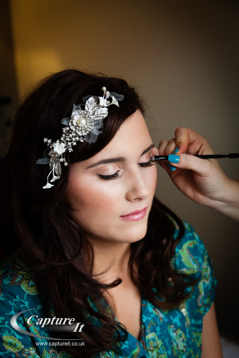 bride having makeup put on before wedding