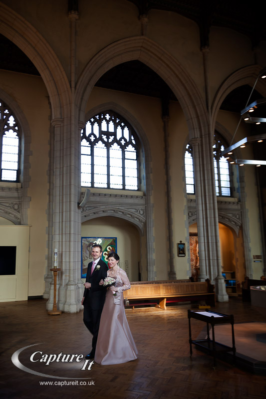 couple walk up the ailse for their blessing