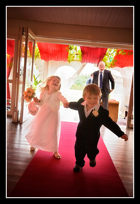 Pageboy and bridesmaid run up aisle
