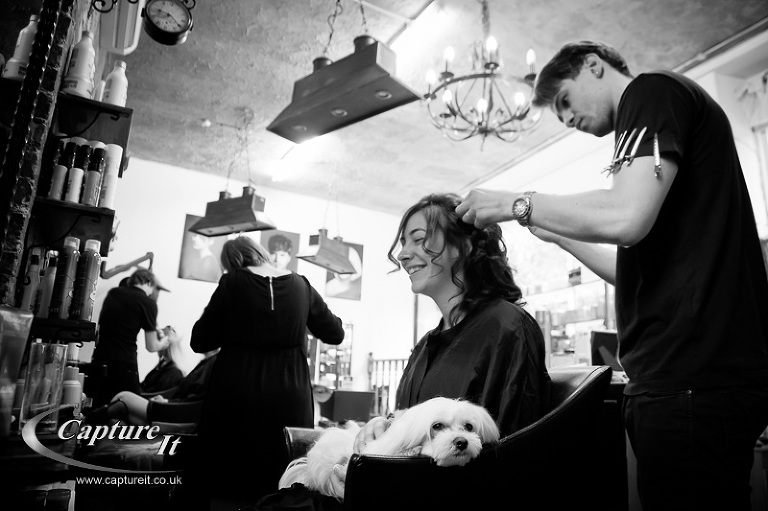 bride at the hairdressers while a dog sits on her lap unimpressed