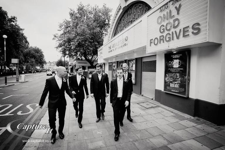 groomsmen walk past a cinema sign saying only god forgives
