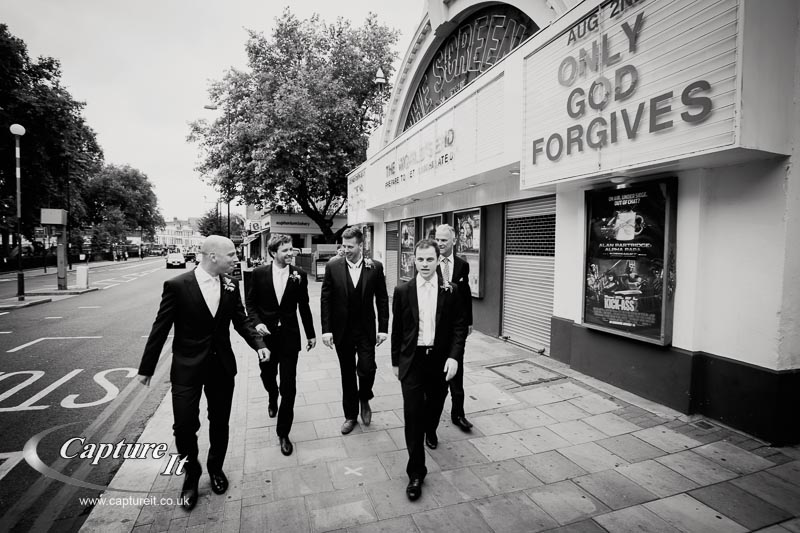 groomsmen walk past a cinema sign saying only god forgives