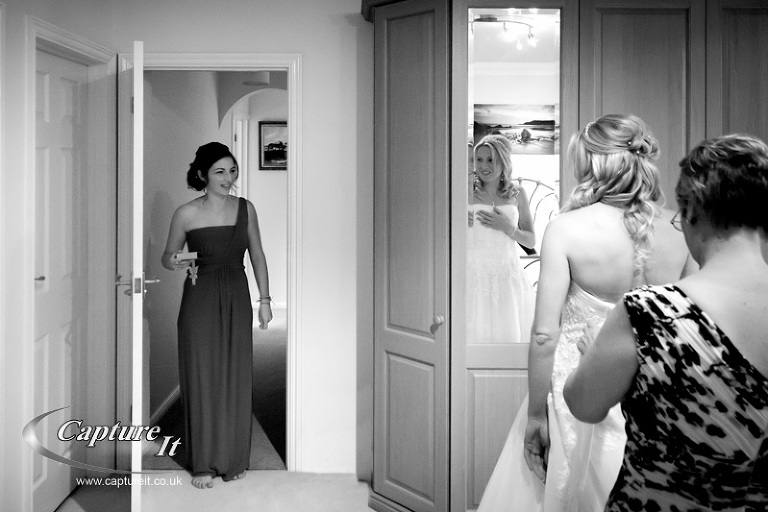 bride puts on dress and looks at bridesmaid