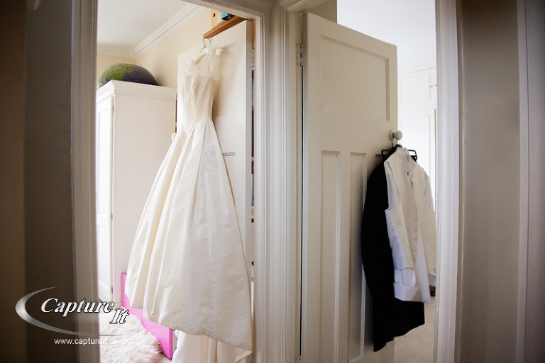 brides dress and father of the bride's suit hanging on two doors