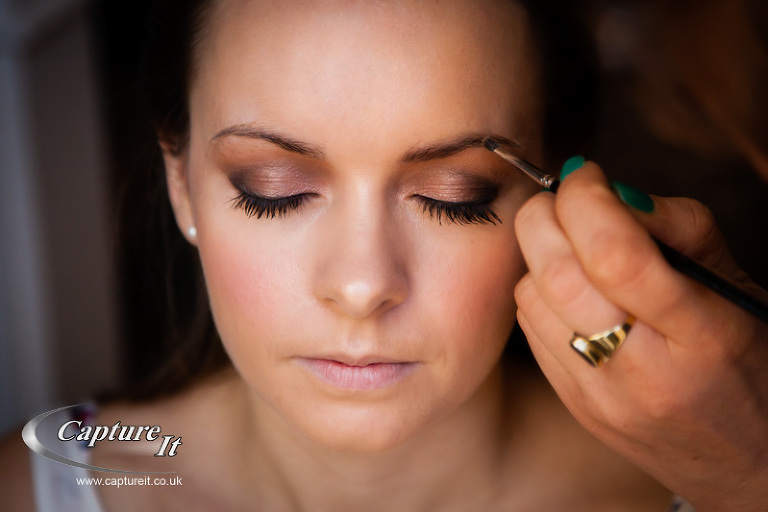 close up of bride having her eyebrows done
