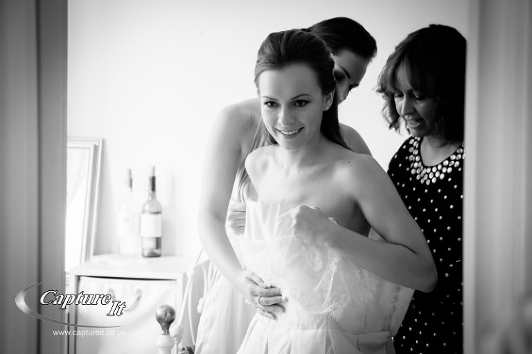 bride putting on her wedding gown