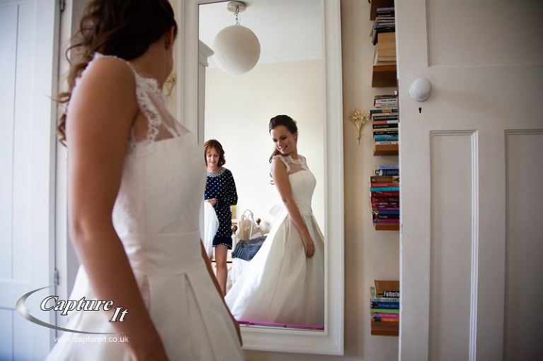 bride looks at herself in her wedding dress in the mirror