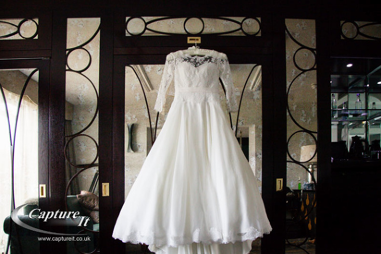 wedding dress hanging from mirrored wardrobe