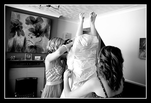 funny shot of bride putting on dress