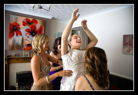 bride laughing putting on dress