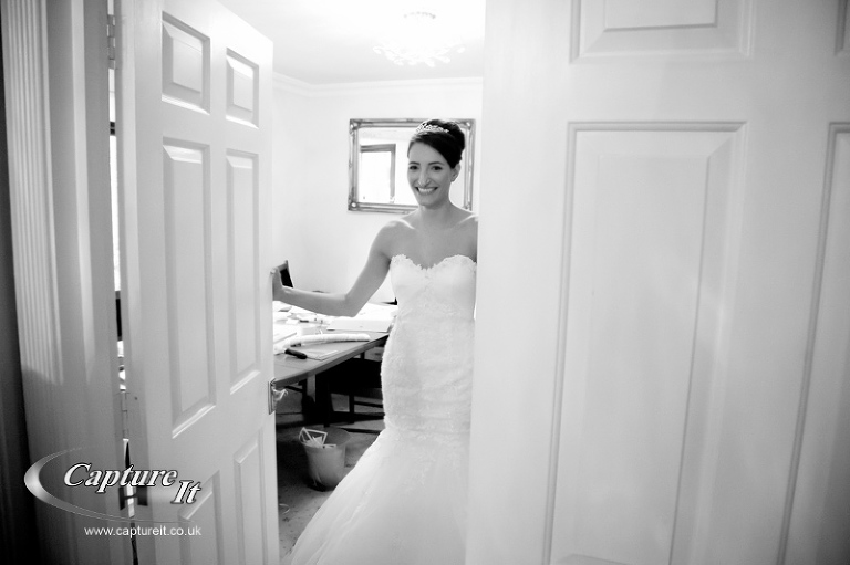 bride opens door to reveal stunning wedding dress