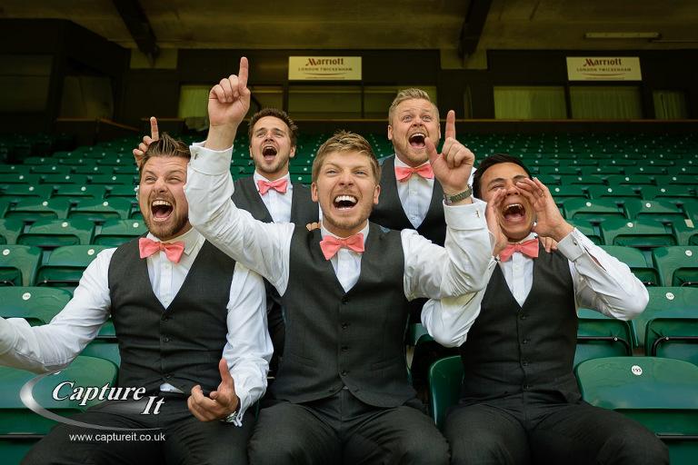 groom and groomsmen cheer at rugby stadium