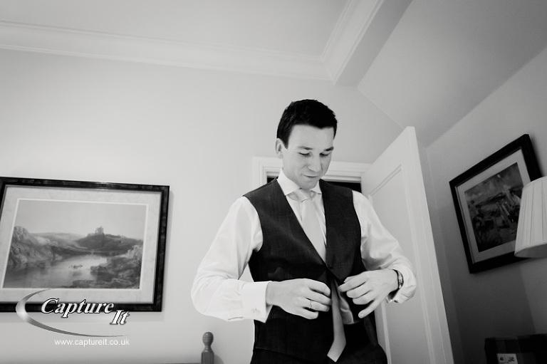 groom puts on his waistcoat
