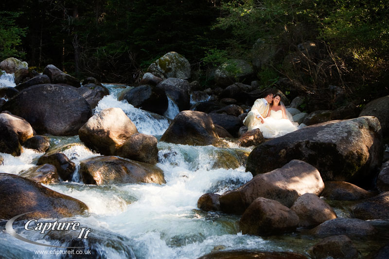 bride and groom sitting on the rocks in a beautiful waterfall