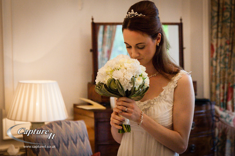 bride admires her bouquet on her wedding day