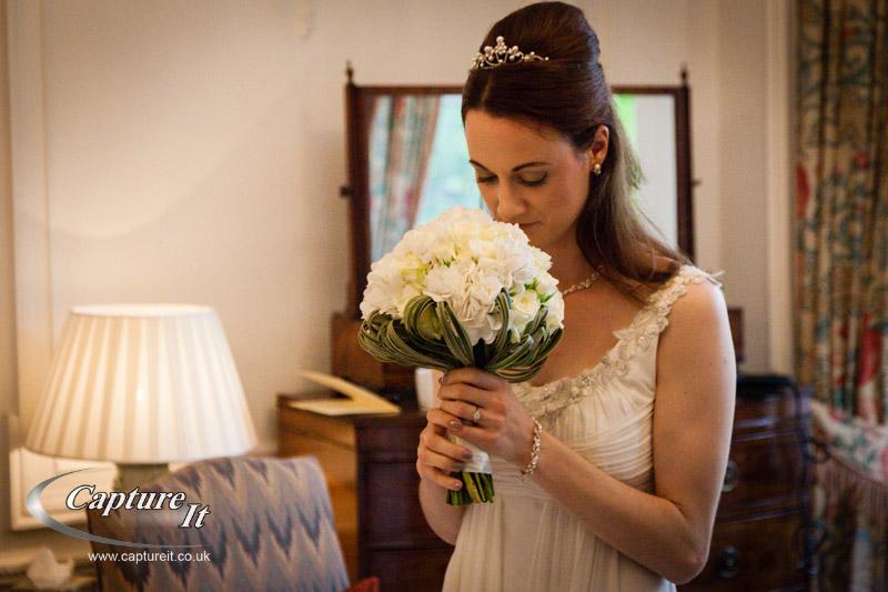 bride admires her bouquet on her wedding day