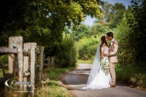 bride and groom kiss down a country lane at gate street barn