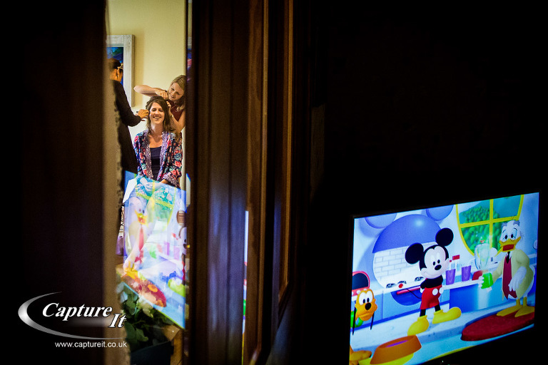 reflection of Mickey Mouse on TV while bride gets her hair done