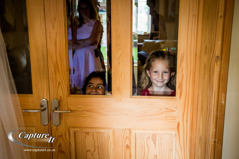 little girls watch through windows as bride has makeup