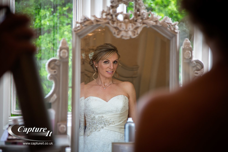 Bride looks at her reflection in the mirror