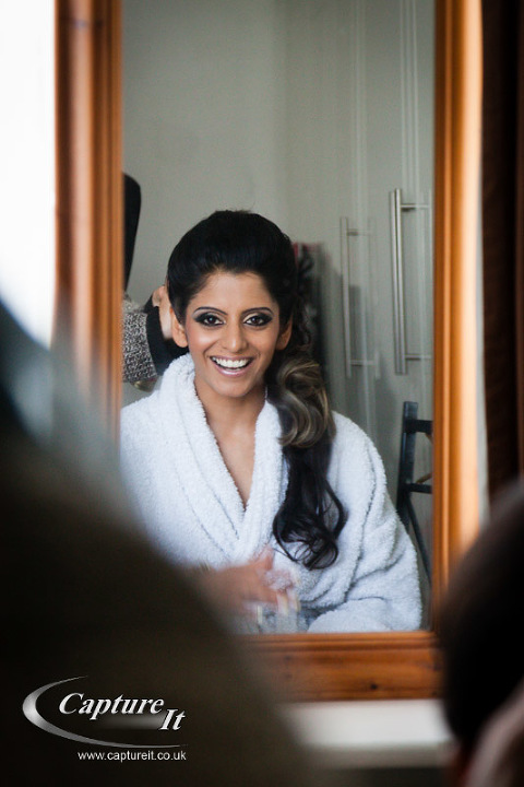 bride smiles at her own reflection while getting ready