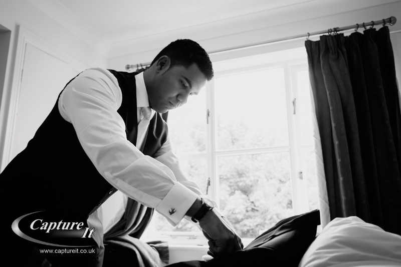 groom adjusts his jacket before wedding