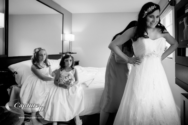 bride putting on dress while flowergirls look on