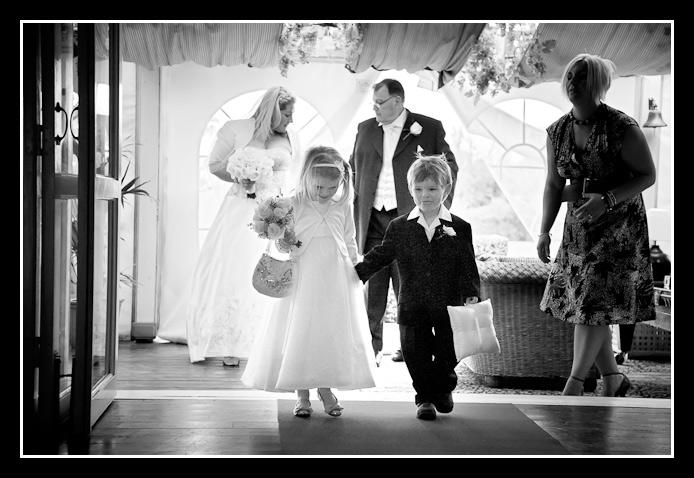 page boy and bridesmaid walk up the aisle