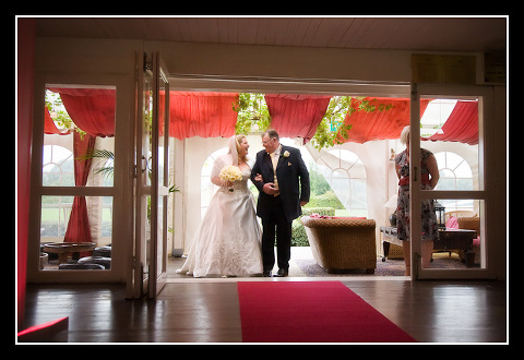 bride and father wait at end of aisle