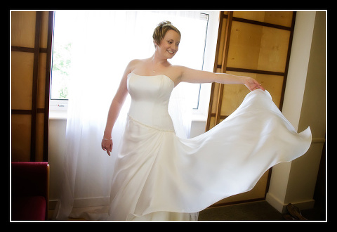 bride playing with wedding gown