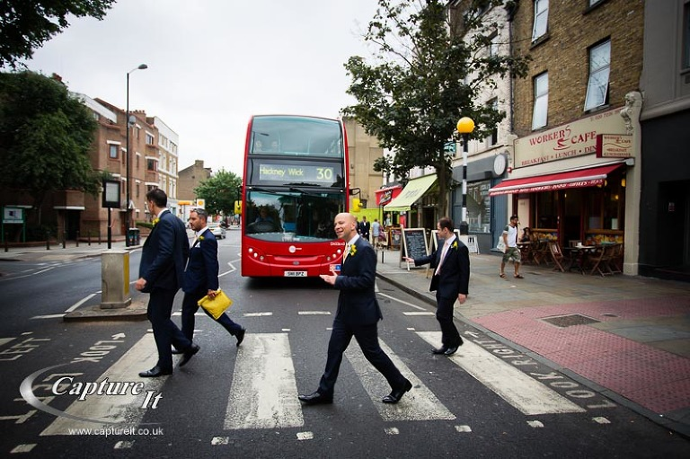 groom and ushers cross in front of a London red bus