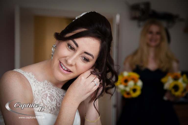 bride puts on an earing with bridesmaid in the background