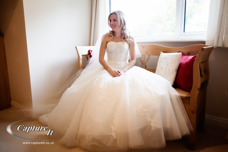 nice picture of bride sitting on a window seat
