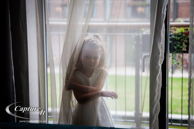 flower girl plays with a net curtain