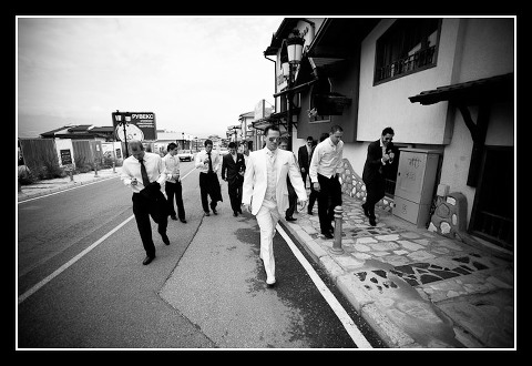 Groom and ushers walk down street in Bansko
