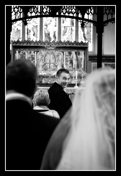 groom waits for bride at end of aisle
