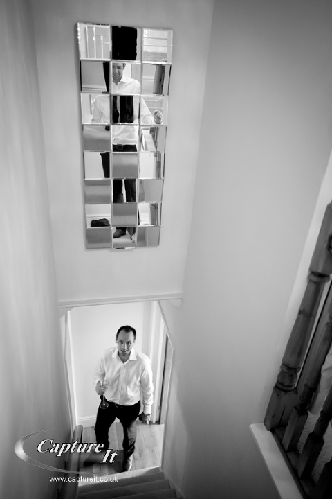 groom looks up at best man reflected in multi-faceted mirror