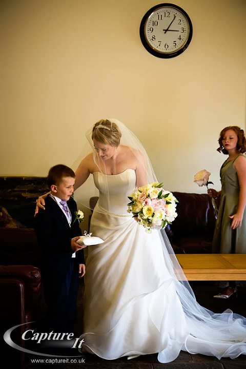 Bride comforts pageboy at a wedding