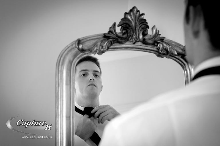groom adjusts his bow tie at wedding